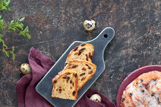 Pão de páscoa (osterbrot em alemão). vista superior do pão fruty tradicional na mesa escura com folhas frescas e ovos de codorna