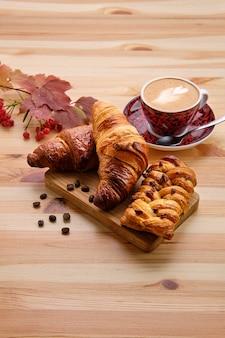 Pão de passas de massa folhada e croissant crocante na mesa de madeira com café