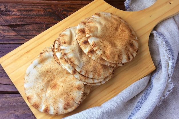 Pão de pita isolado na espátula de madeira saindo do forno