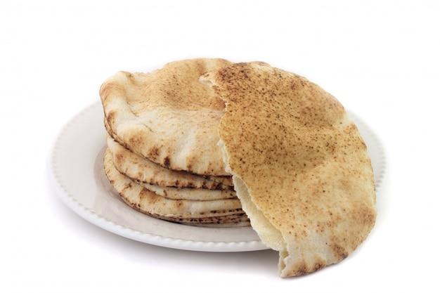 Pão de pita isolado no fundo branco em prato de cerâmica