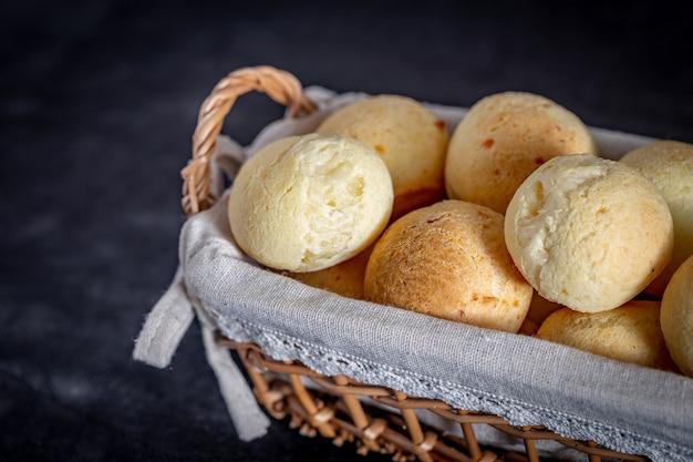 Pão de queijo caseiro brasileiro, aka 'pao de queijo' em uma cesta rústica.