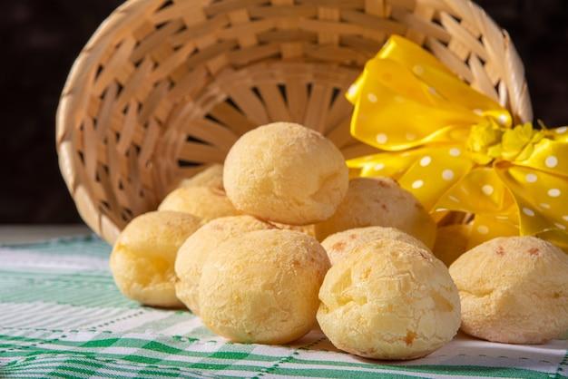 Pão de queijo, cesta de palha com um laço de fita amarela caída com pão de queijo em uma toalha de mesa quadriculada.