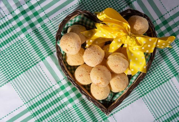 Pão de queijo, cesta em forma de coração com um laço de fita amarela cheia de pão de queijo em uma toalha de mesa quadriculada, vista de cima.