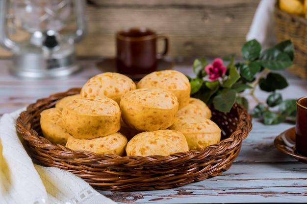 Pão de queijo, chipa com café e flores.