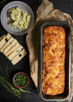 Pão de queijo com manteiga de ervas em um prato de madeira com ervas