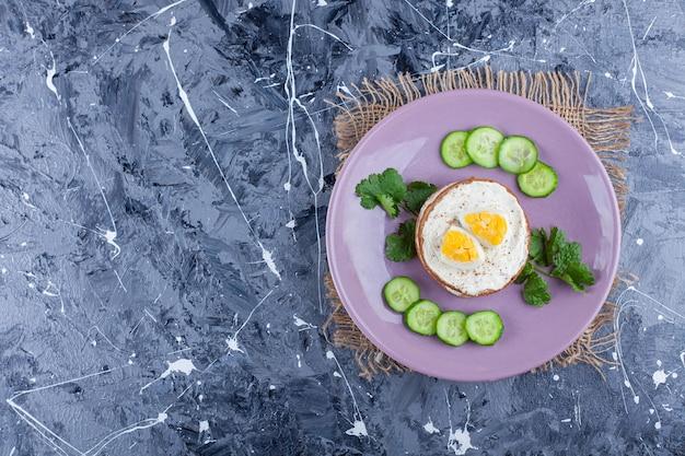 Pão de queijo fatiado ao lado de pepino picado e salsa em um prato, sobre o fundo azul.