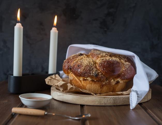 Pão de sweet chalá em um prato redondo arborizado na mesa de madeira marrom com mel e duas velas na noite de shabat tornando kidush