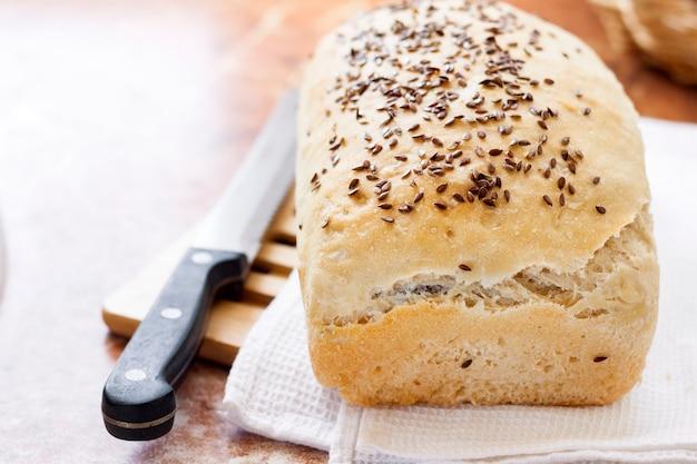 Pão de trigo caseiro com sementes de linho na mesa da cozinha