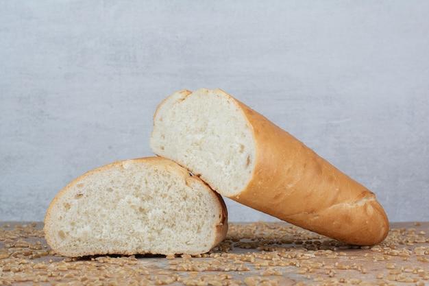 Pão de trigo cortado pela metade com cevada na mesa de mármore