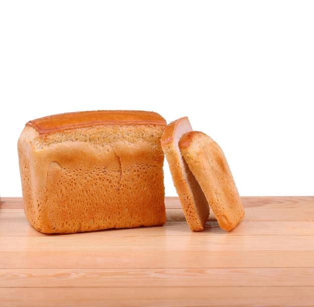 Pão de trigo fresco fatiado em uma placa de cozinha sobre o branco