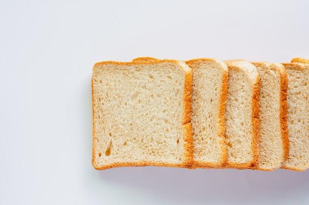 Pão de trigo integral bem cortado em fundo branco