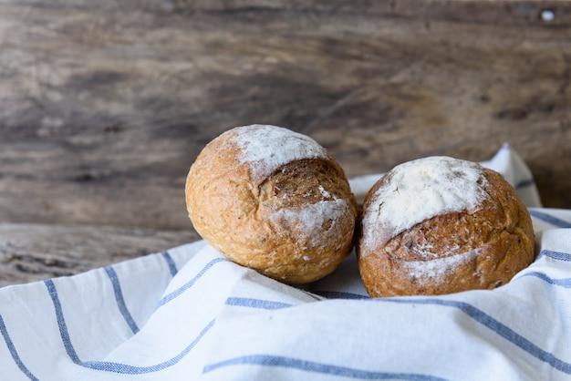 Pão de trigo integral colocado em uma cesta de bambu na mesa de madeira
