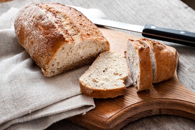 Pão de trigo integral com fatias na placa de madeira