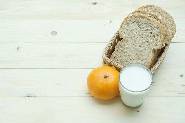 Pão de trigo integral no cesto com fruta laranja e leite na mesa de madeira