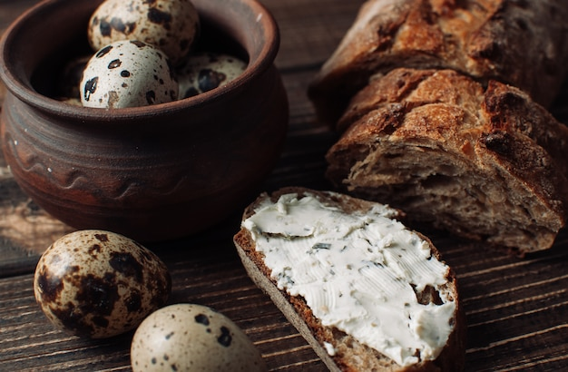 Pão de trigo sarraceno escuro é espalhado com queijo cottage com ervas em um corte sobre uma mesa de madeira perto de ovos de codorna em um prato de barro em estilo rústico.