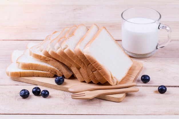 Pão de trigo torrado fatiado e leite de vaca na madeira