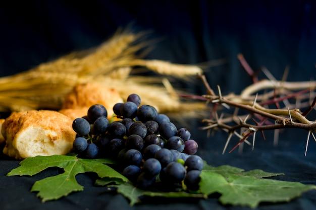 Pão de uvas do trigo e coroa de espinhos em fundo preto