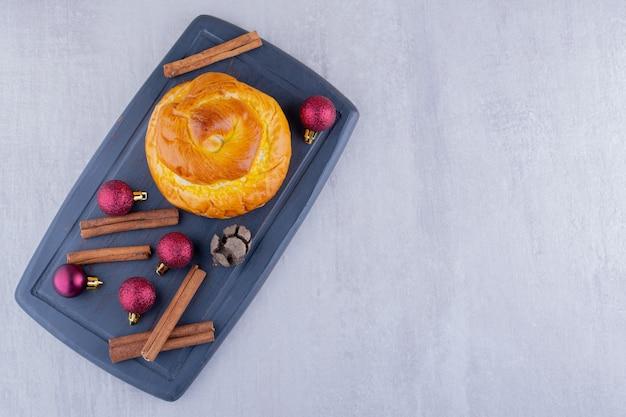 Pão delicioso, cone de cipreste, paus de canela e decorações de natal em fundo branco.