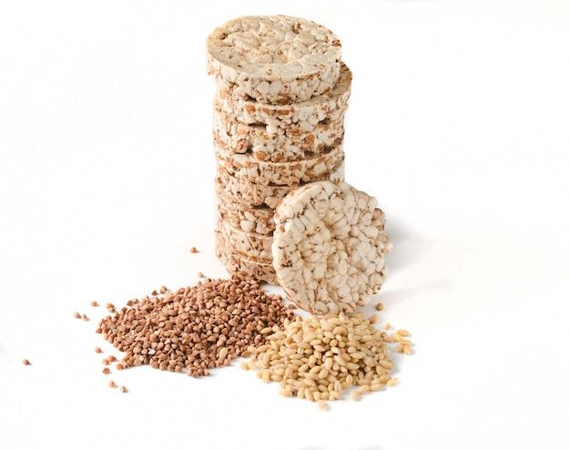 Pão dietético redondo friável da aptidão do arroz do trigo mourisco isolado no fundo branco. alimento para perda de peso.
