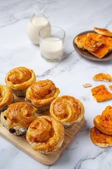 Pão dinamarquês fresco com leite e frutas, mirtilo, molho de cereja servido com leite.