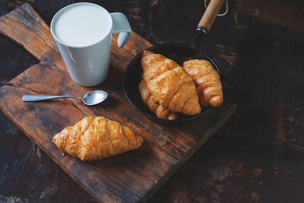 Pão do café da manhã, croissants e leite fresco na mesa de madeira.