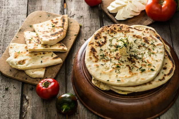 Pão do pão árabe na placa de madeira com queijo de feta e tomates e pimenta. ainda vida de comida. g