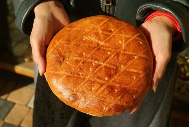 Pão doce armênio cozido fresco chamado gata nas mãos da mulher