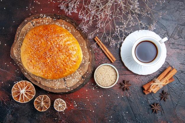Pão doce assado com uma xícara de chá na superfície escura