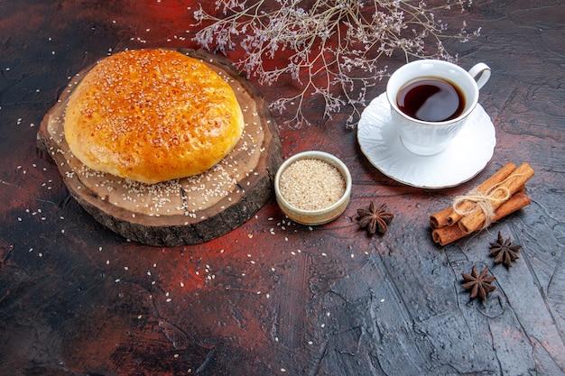 Pão doce assado de frente com uma xícara de chá em fundo escuro