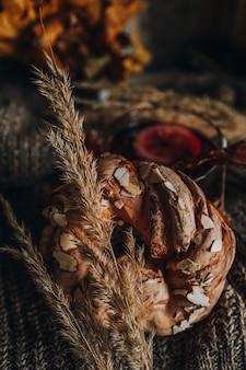 Pão doce com amêndoas deitado sobre um tecido de malha com flores secas de outono. casa aconchegante ainda vida