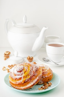 Pão doce com mel, nozes e coco ralado em fundo branco.