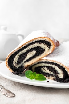 Pão doce com sementes de papoula da massa de fermento polvilhada com açúcar de confeiteiro corte ao meio mentiras em um prato branco decorado com um raminho de hortelã feito em casa no fundo está um bule de porcelana branca