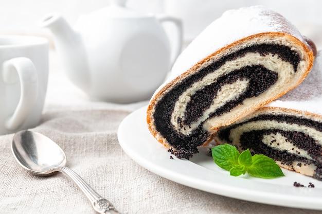 Pão doce com sementes de papoula da massa de fermento polvilhada com açúcar de confeiteiro corte ao meio mentiras em um prato branco decorado com um raminho de hortelã