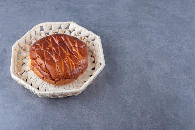 Pão doce e macio em cesto de vime, no mármore.