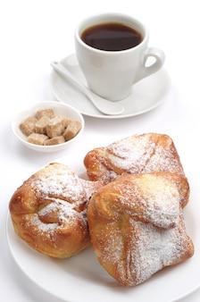 Pão doce e xícara de café no fundo branco