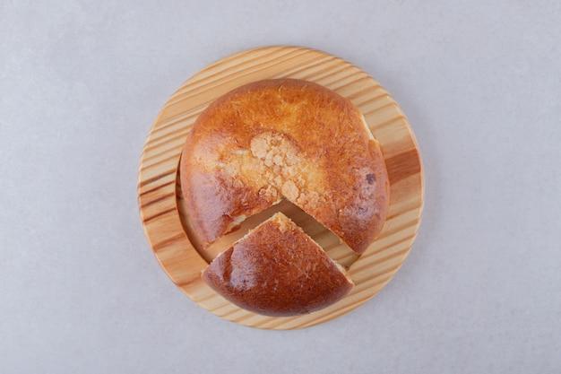 Pão doce fatiado na placa de madeira na mesa de mármore.
