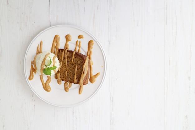 Pão doce marrom delicioso com sorvete branco em uma mesa branca