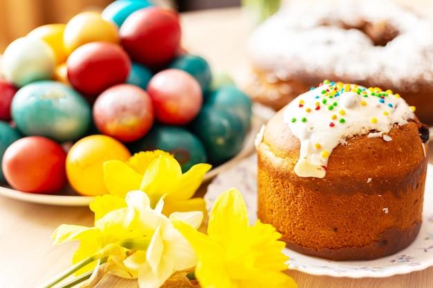Pão doce ortodoxo da páscoa, kulich, ovos coloridos e um buquê de narcisos. luz do sol brilhante. café da manhã tradicional da páscoa. foco seletivo.