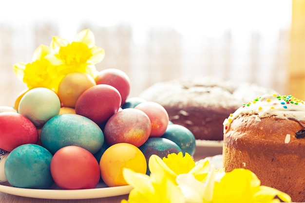 Pão doce ortodoxo da páscoa, kulich, ovos coloridos e um buquê de narcisos. luz do sol brilhante. café da manhã tradicional da páscoa.