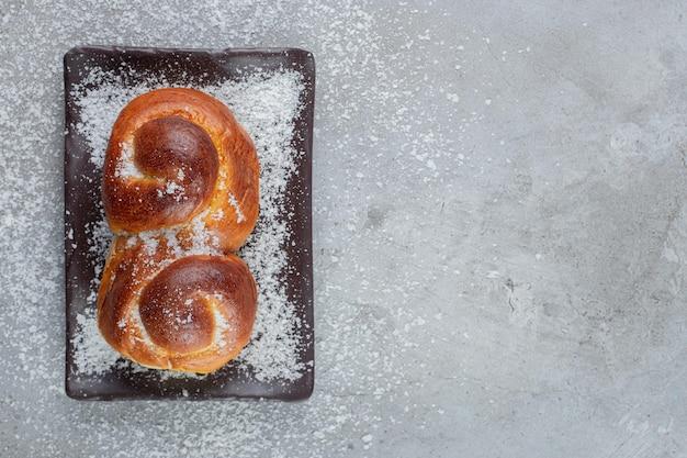 Pão doce recheado com geléia em uma travessa na mesa de mármore.
