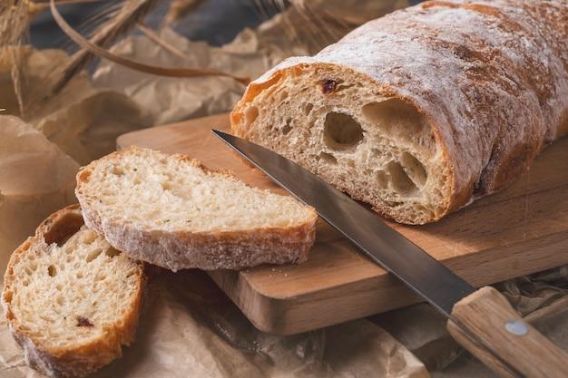 Pão duro de ciabatta pronto para comer. pão fresco de ciabatta na tábua de madeira.