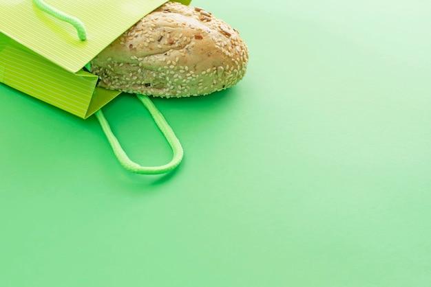 Pão duro fresco no saco de compras em um fundo verde.