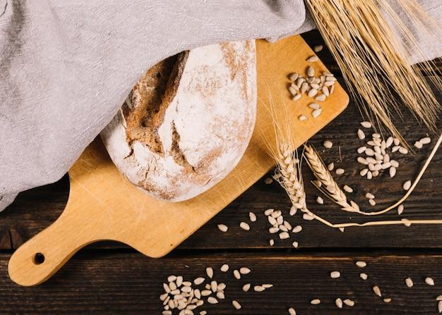 Pão e espiga de trigo com sementes de girassol na mesa de madeira escura