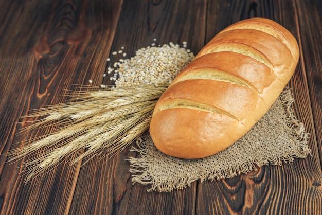 Pão e espigas de grão no fundo escuro de madeira.
