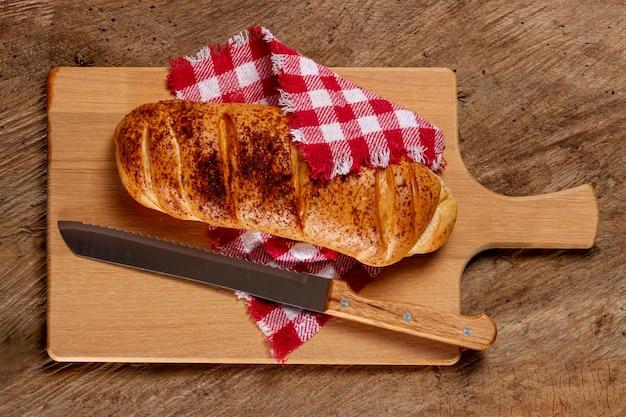 Pão e faca na placa de madeira