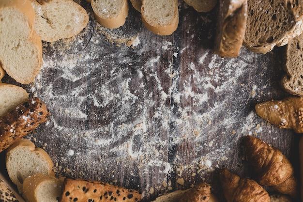 Pão e farinha de pastelaria em uma mesa de madeira