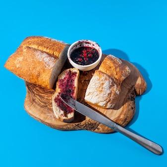 Pão e geléia com sobras de migalhas na tábua de madeira