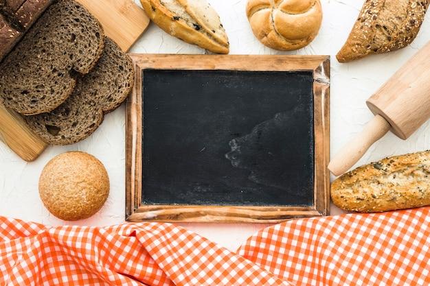 Pão e rolo perto de lousa e pano