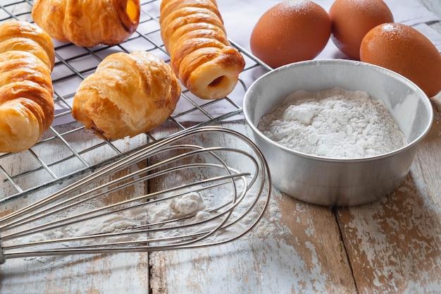 Pão e tigela de farinha no fundo de madeira