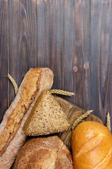 Pão e trigo em branco de madeira.